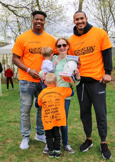 Patriots defensive linemen Keionta Davis (left) and Derek Rivers (right) present Foxborough resident Erin Coombs (center) with an autographed Rob Gronkowski football at Saturday's seventh annual Clean Up Foxboro Day. Coombs won the football, donated by the Kraft Group, during the event's raffle.