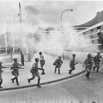 Police on the run after firing tear gas to disperse left-wing demonstrators at Tung Tau Estate. 12 May 1967 Byline: Chan Kiu Credit: SCMP
