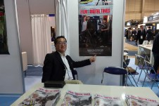 Angenieux's Yasuhiko Mikami with EZ zoom poster at FDTimes booth