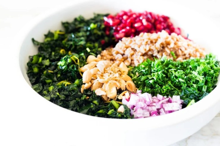 Healthy Vegan Kale Farro Salad with Almonds and Pomegranate Seeds. Think of this like a Winter Tabbouleh- lemony light and flavorful, this easy Middle Eastern-inspired salad can be made ahead, perfect for mid-week lunches. #healthykalesalad #kalesalad #vegansalad #vegankalesalad #farrosalad #tabouli #tabbouleh