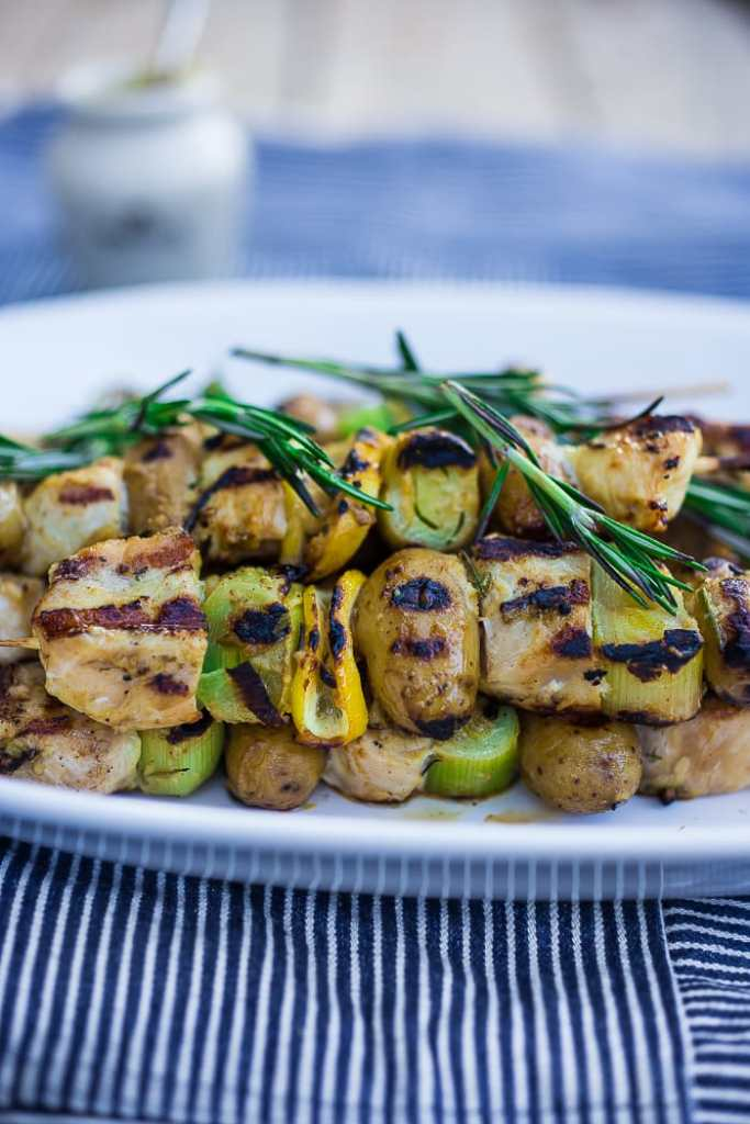 ... Chicken Skewers with Leeks on a platter with rosemary sprigs and lemon