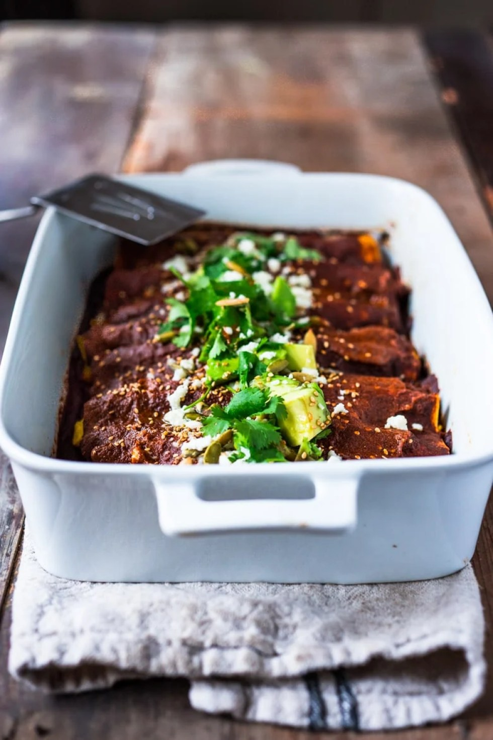 15 Cozy Fall Dinners that are MEATLESS!  Roasted Butternut Mole Enchiladas with Blackbeans - topped with cilantro, avocado and toasted sesame and pumpkin seeds. An easy delicious vegetarian main.   www.feastingathome.com