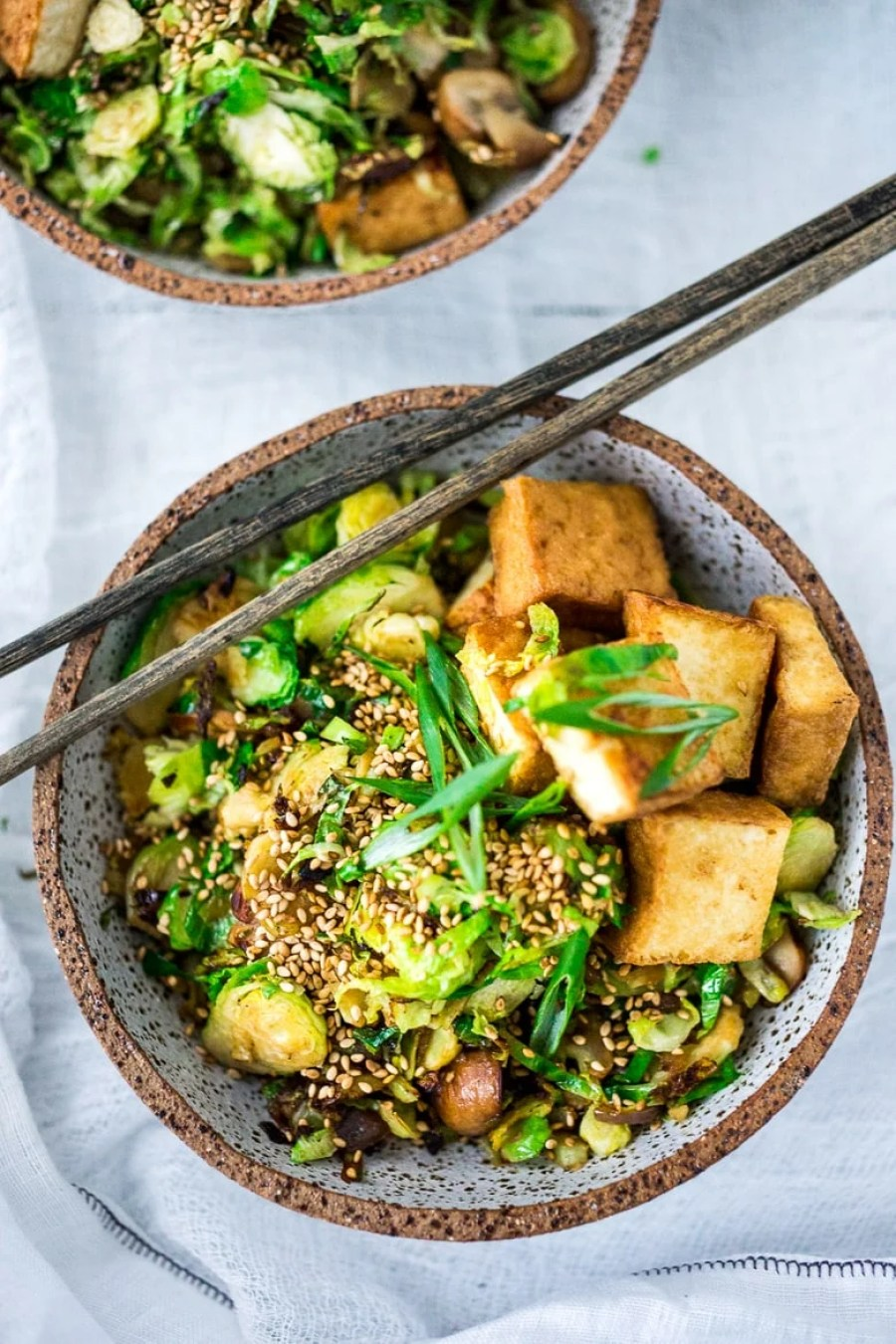EAT CLEAN with these 20 simple Plant-Based Meals!!!   Sesame Brussel Sprouts and Tofu Bowl- with mushrooms, scallions and toasted sesame seeds. Vegan and Gluten-free.   www.feastingathome.com
