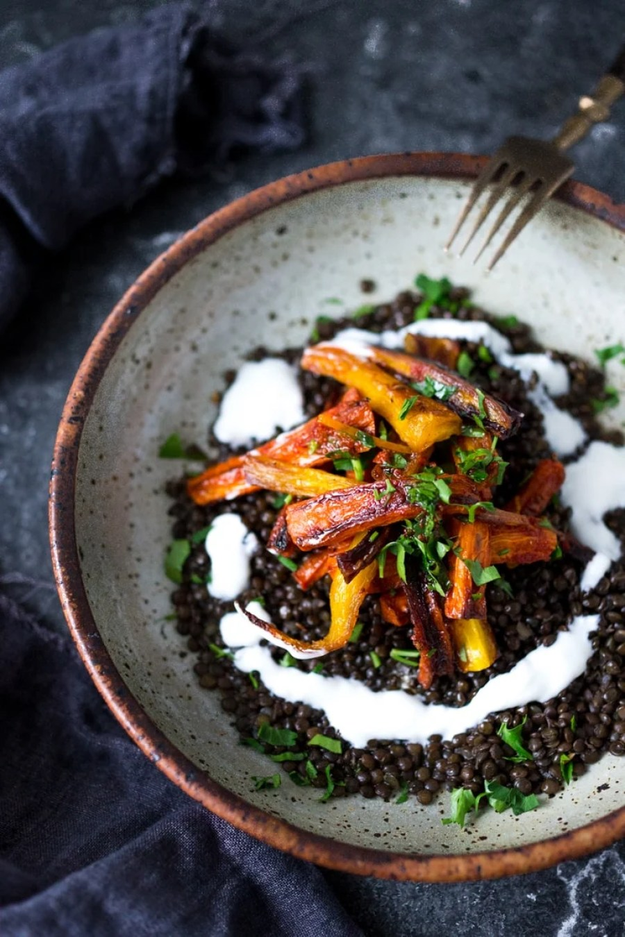 EAT CLEAN with these 20 simple Plant-Based Meals!!!  Roasted Moroccan Carrots over seasoned lentils for a hearty vegetarian meal.   www.feastingathome.com