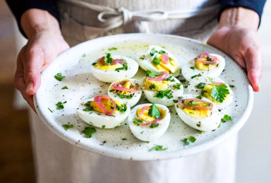 Simple Boiled Eggs with olive oil, herbs and pickled shallots- a fast and tasty way to use up all your Easter Eggs or feed a crowd. | www.feastingathome.com