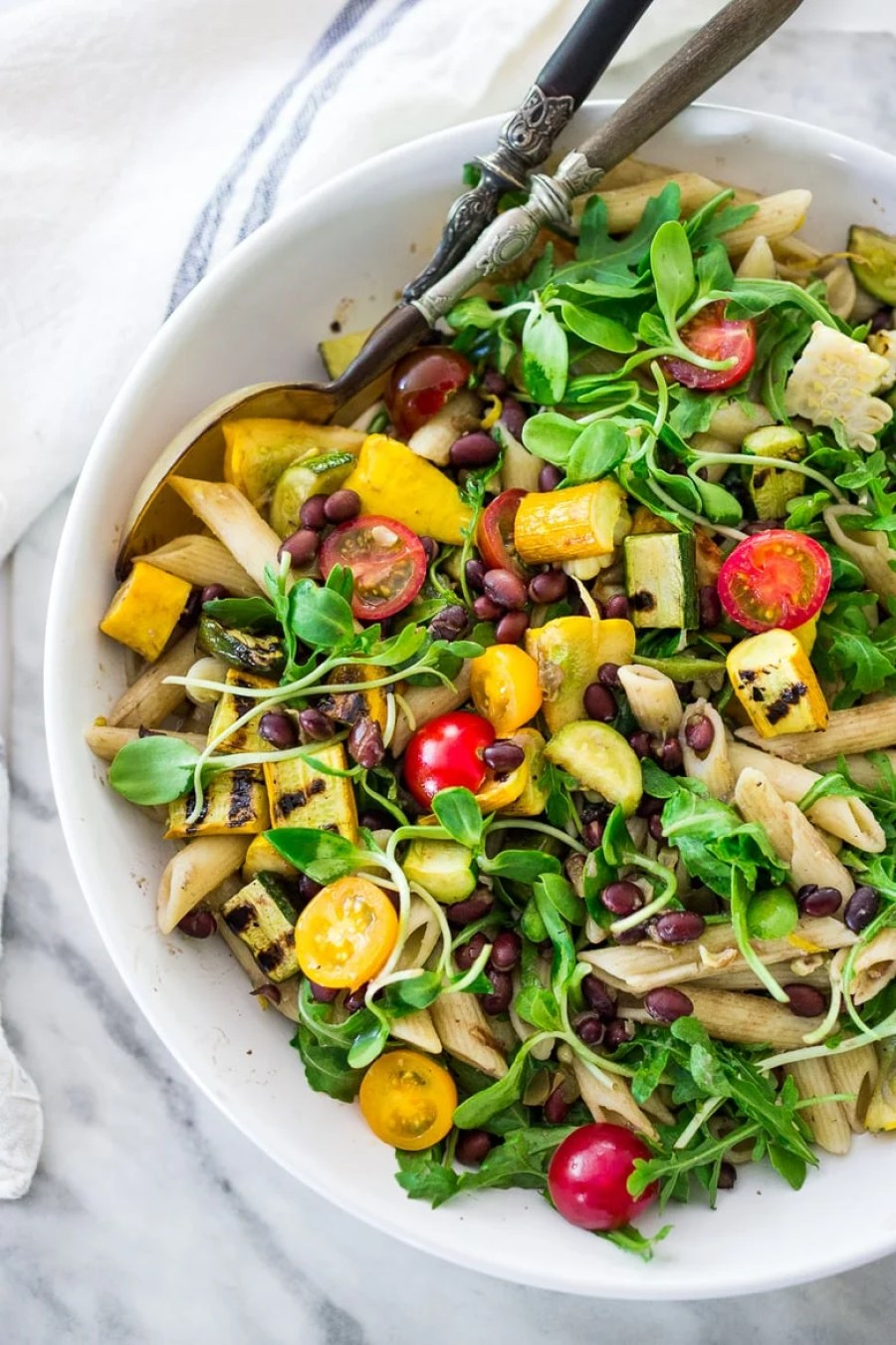Farmers Market Veggie Pasta with grilled zucchini, corn and blackbeans or other veggies! Make with optional grain-free pasta and keep it vegan or add feta. | www.feastingathome.com