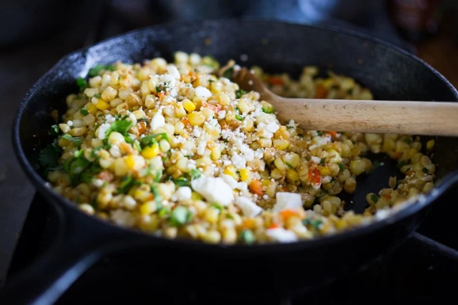 Mexican Street Corn with chilies, cilantro and lime - also called Elotes. This lighter version can be grilled or sautéed and can easily be made vegan! | www.feastingathome.com