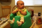 Meg at dinner in the bumbo chair