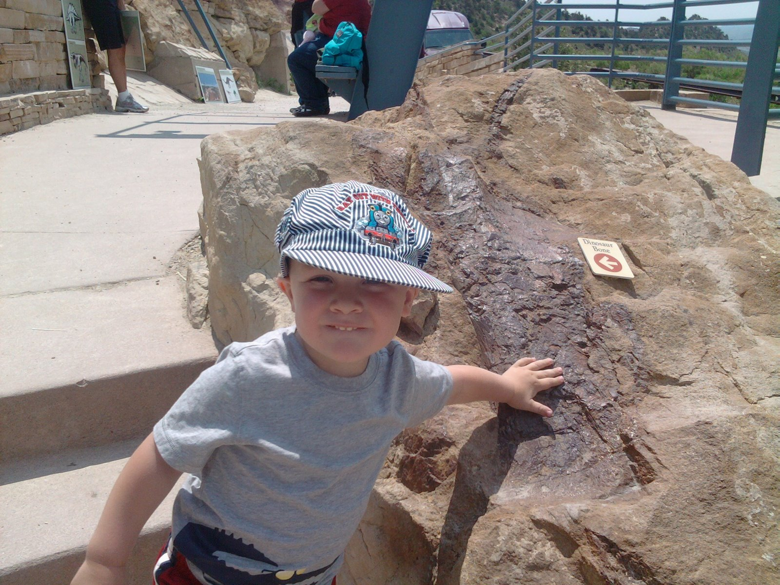 Spencer touching a fossil at Dinosaur Ridge