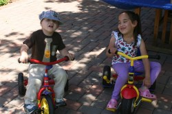 Spencer and Camilla riding tricycles