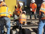 Workers connecting the tracks with a giant wrench