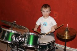 Spencer playing his new drumset