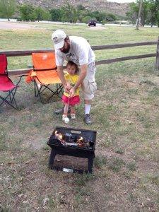Daddy teaching Meg how to roast marshmallows