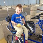 Spencer enjoying mac n cheese on a bicycle built for two (or three)