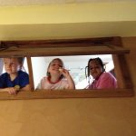 Sadie, Spencer, and Meg smiling through the window to upstairs.