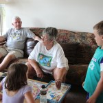 Meg, Grandma, and Spencer playing monopoly