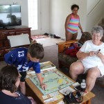 Spencer playing monopoly with Clare and onlookers
