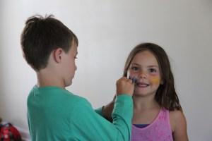 Spencer paints Meg's face maize and blue