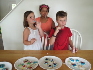 Meg, Sadie, and Spencer licking their frosting knives