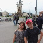Spencer and Meg by statue at Plaza de Espanya