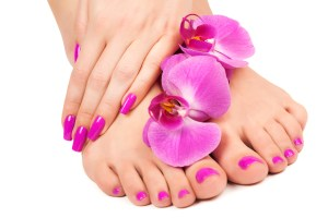 Relaxing pink manicure and pedicure with a orchid flower
