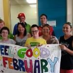This is an image of clients and staff from RLOA holding a colourful Feel Good February banner