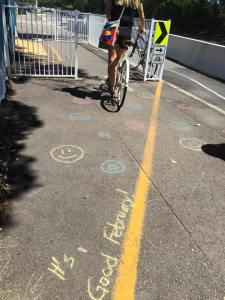 This is an image of smiley faces and kindness saying in chalk outside Manly swim centre