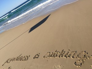This is an image of Kindness Is Catching written in the sand