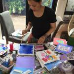 This is an image of Linda Pang working on some paintings for FGF 2016