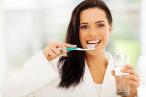 woman holding toothbrush and water