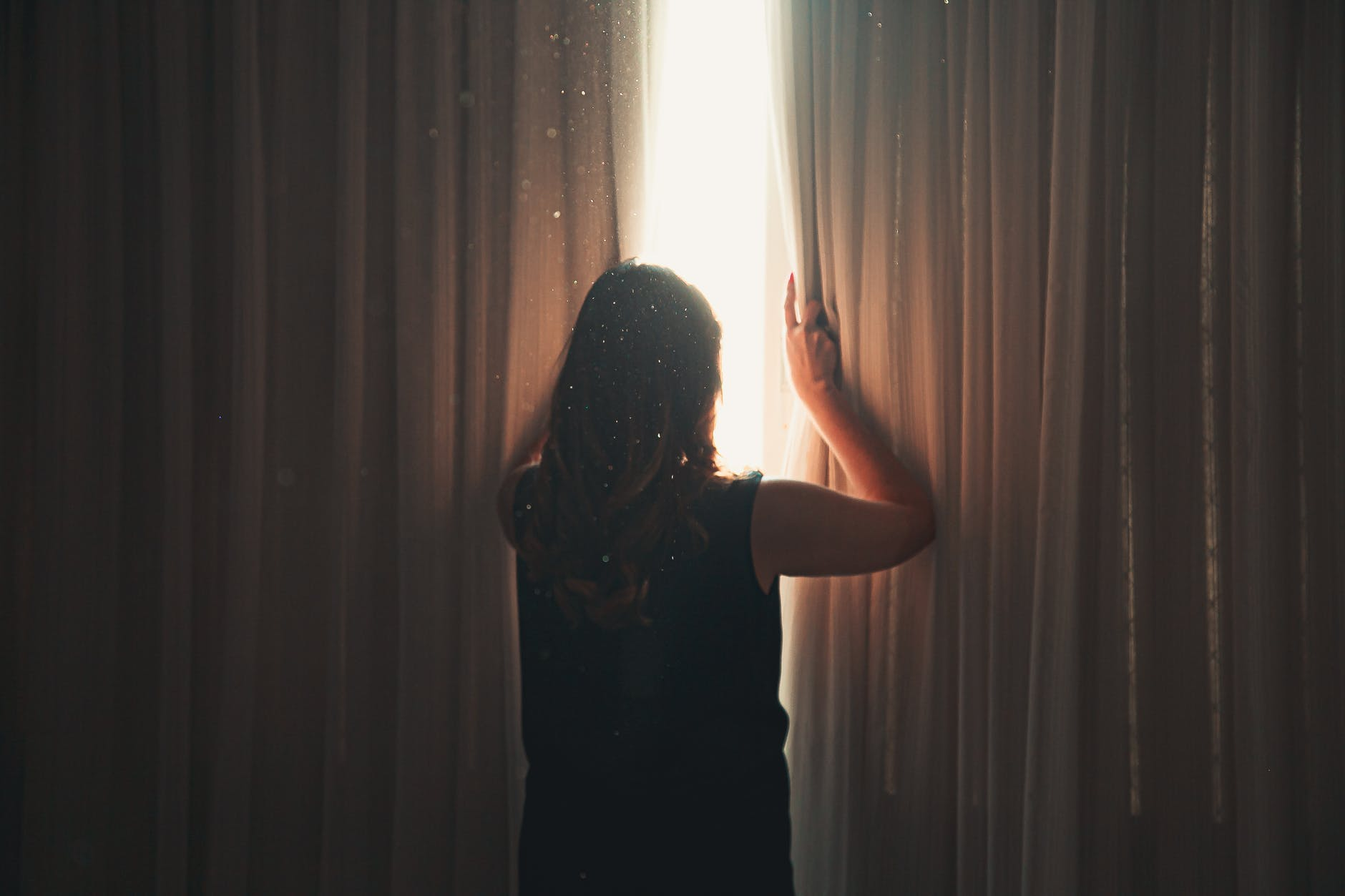Unrecognizable woman opening window curtain in shining daylight