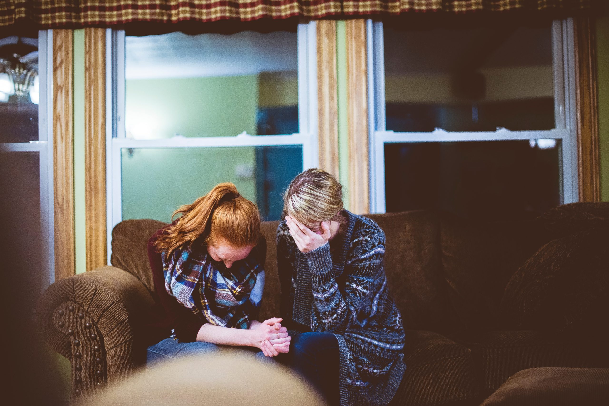 Two women sitting on a couch who are upset and crying