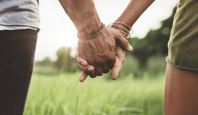 Two people holding hands in a field