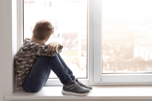 Young child holding his legs and looking out the window