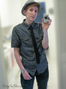 Taylor as a fresh-faced young trans guy. Posing wearing a grey short-sleeved button down, black tie, watch, and grey hat, taking a picture in the mirror