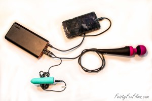 A portable charger (left) with multiple devices plugged into it (right). From top to bottom, the devices are a Samsung S5 Neo phone, the PalmPower Recharge vibrator, and the Vi-Do BAM bullet vibrator