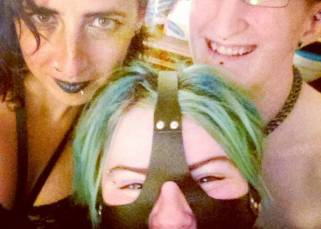 Lizxnn, top left, smirking, her hair falling over her right eye, wearing a blue/black lipstick and a black dress. Taylor, top right, is naked except their collar, grinning happily. Sugar Cunt, cottom center, is wearing a nuzzle but they are squinting in a way that shows they are smiling.