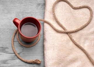 Coffee and Kink's logo; a full, red coffee mug sits on light grey wood. next to it there is tan, soft-looking fabric. On top of the fabric there is some undyed rope on top of the fabric that is bent int a heart shape before forming a loop around the coffee mug.