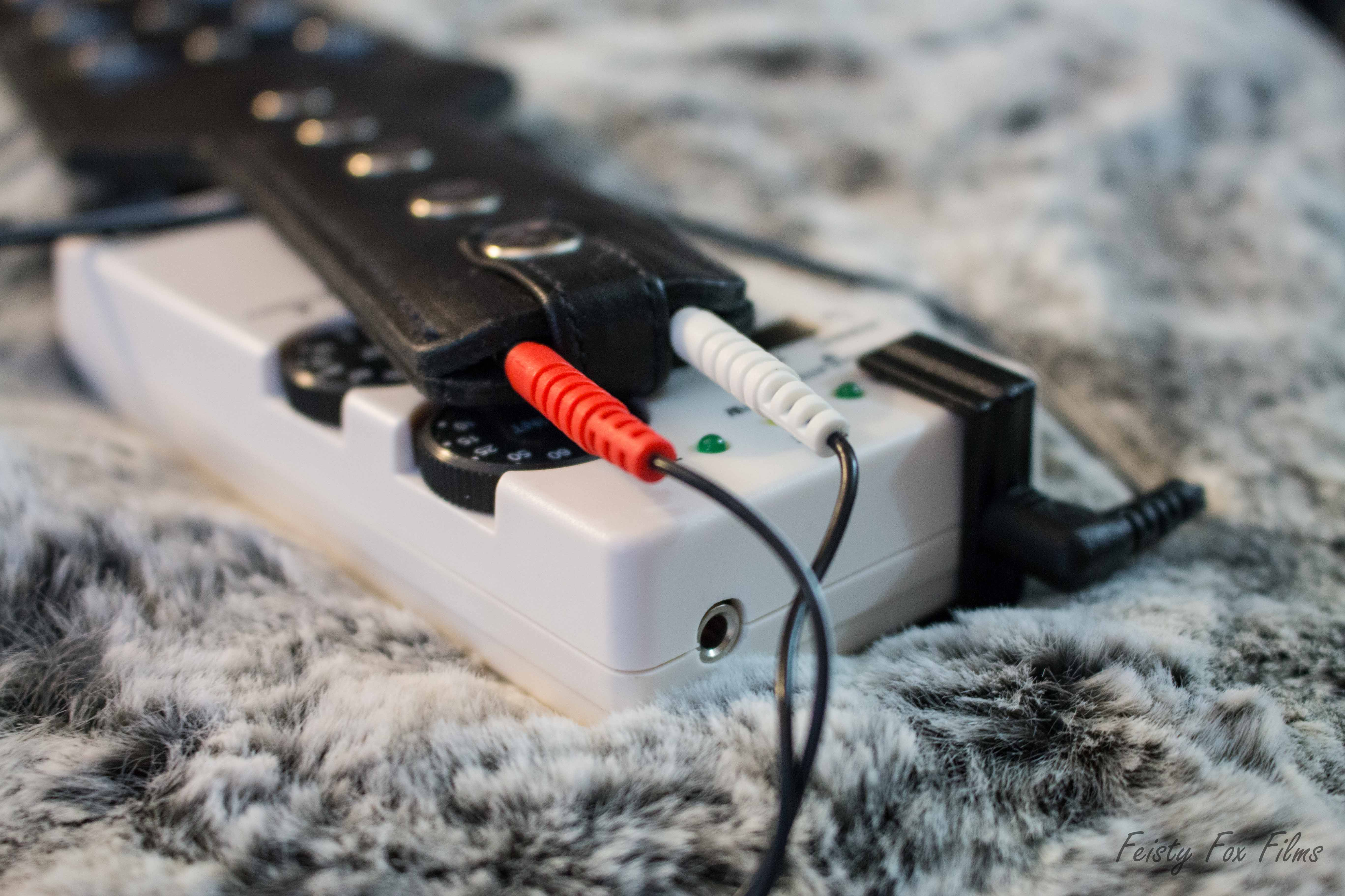 The Electro Spanking Paddle sits on top of an estim power box, which rests on top of a grey and white fake fur fabric. The shot is in focus around the handle of the paddle, where two supply cables are connected. the cord disappears out of the shot and then reappears to plug in to the power box. The box's lights aren't lit, indicating that the paddle is plugged in but not turned on.