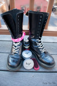 Tall black Doc Martins are sitting mostly unlaced on a deck. They are shiny, though a bit scuffed up, and their laces are white. Between the two shoes are a small pile of boot blacking materials. Attached around the ankle of one of the boots is a light pink collar with white dog bones on it.