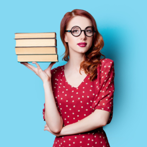 A very pretty redhead stands holding four books by her head. Her hair is just past her shoulders and wavy, pulled to one side. She is wearing large framed blackglasses, red lipstick, and a red dress with white polka dots.