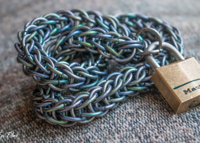 """A chainmail collar lies curled up on a couch. It is held together with a lock that says """"MASTER"""""""