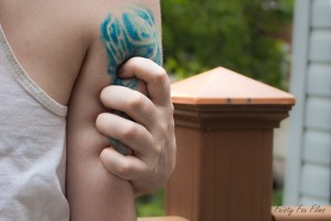 Closeup of the back of Taylor's forearm showing a blue whispy tattoo. Their other hand is squeezing their arm, fingers digging in to the area where the tattoo is. You can see trees and a post in the background.