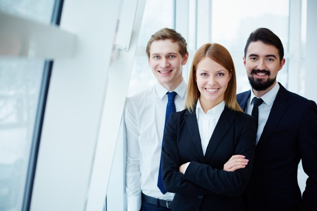 companeros-de-trabajo-felices-junto-a-la-ventana_1098-3172