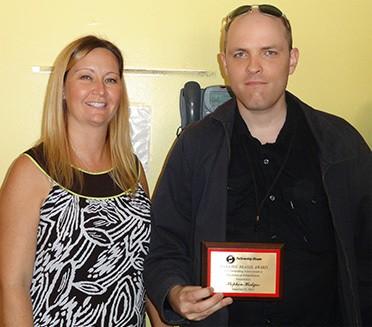 photo of a Fellowship House client with an award