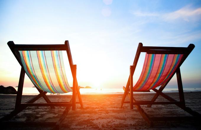 Pair of beach loungers on the deserted coast sea