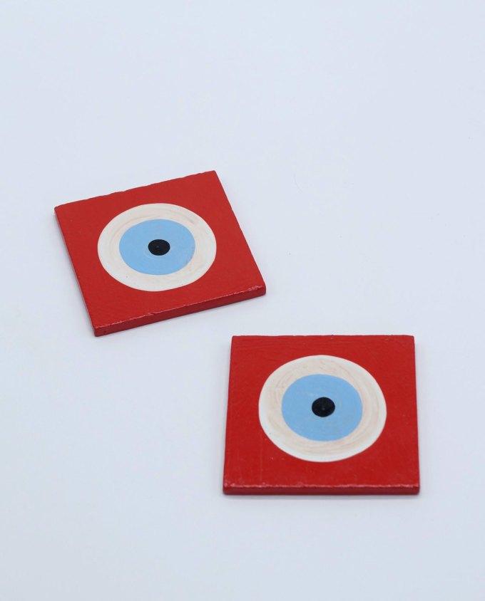 A handmade wooden red evil eye coaster