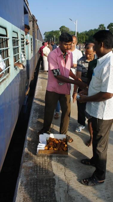 Verhungern und verdursten tut man in indischen Zügen definitiv nicht. Ständig kommt jemand mit Nüssen, Chips, Wasser, Chai, usw. vorbei. Das warme Essen wird in den Bahnhöfen zubereitet und beim Zwischenhalt auf dem Bahnsteig ausgereicht (wie auf diesem Bild zu sehen). Manche Züge haben auch einen Speisewagen, in dem jedoch nur gekocht wird. Das Essen wird dann an den Platz gebracht