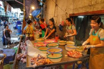 Unweit der Hochhäuser, die Bangkoks Silhouette prägen, befindet sich der große Khlong Toei-Markt. Hier wird alles denkbar Essbare - von Keksen bis zu lebenden Hühnern - Feil geboten. Das Fleisch kommt frisch vom Metzger. Die Frauen haben ihren Spaß daran, das arme Schwein (oder wars doch ein Rind?) auseinanderzunehmen