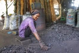 Eigentlich sind alle Arbeitsschritte bei der Herstellung von Holzkohle alles andere als ein Zuckerschlecken. Sei es das Füllen der Öfen mit den schweren Stämmen, das Ausräumen oder wie hier - das Sortieren der Reste, um die Stücke herauszufiltern, die noch verkauft werden können. Nach eineinhalb Stunden in der Nähe der Öfen sehnte sich meine Lunge nach frischer Luft. Ich frage mich, wie es die Menschen hier tagtäglich aushalten. Übrigens: Die Frau hatte Spaß an ihrer Arbeit - und lachte!
